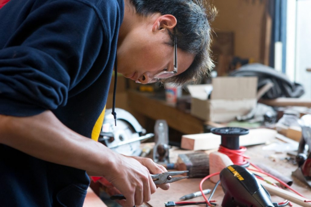 High School age Asian male cutting wires in technical class