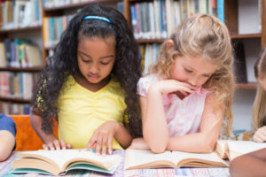 Approximately five year old African American girl reading with approximately five year old Caucasian girl with blonde hair in library.